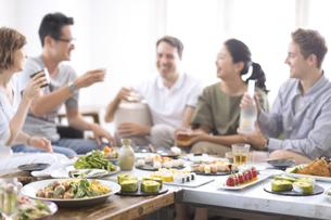 ホームパーティーを楽しむ外国人と日本人の写真素材 [FYI03114676]