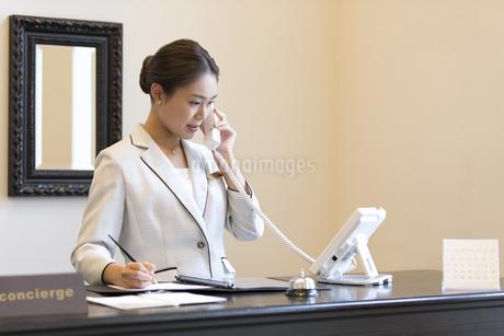電話対応をするコンシェルジュの女性の写真素材 [FYI03114677]