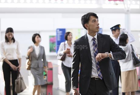 駅の改札付近で時計を見るビジネス男性の写真素材 [FYI03114679]