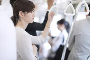 電車で外の景色を見つめるビジネス女性の写真素材 [FYI03114683]