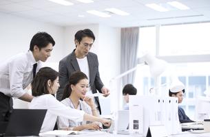 パソコンを見て打ち合わせをする男女4人のビジネスマンの写真素材 [FYI03114691]