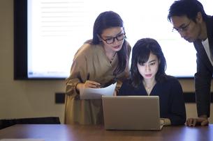 パソコンを見て打ち合わせをする男女3人のビジネスマンの写真素材 [FYI03114692]