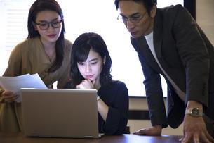 パソコンを見て打ち合わせをする男女3人のビジネスマンの写真素材 [FYI03114698]