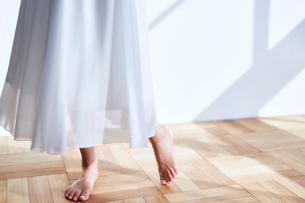 シンプルな部屋を裸足で歩くレーススカートの女性の写真素材 [FYI03114814]