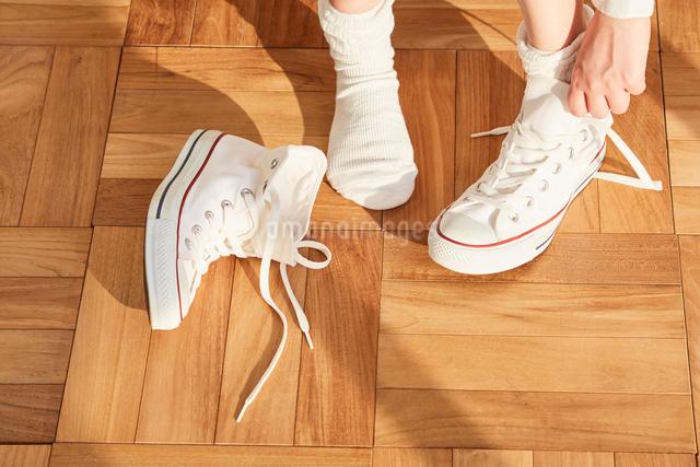 白いスニーカーを履く女性の足元の写真素材 [FYI03114819]