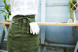 作業台の前に立つ女性の園芸をするエプロン姿の写真素材 [FYI03114820]