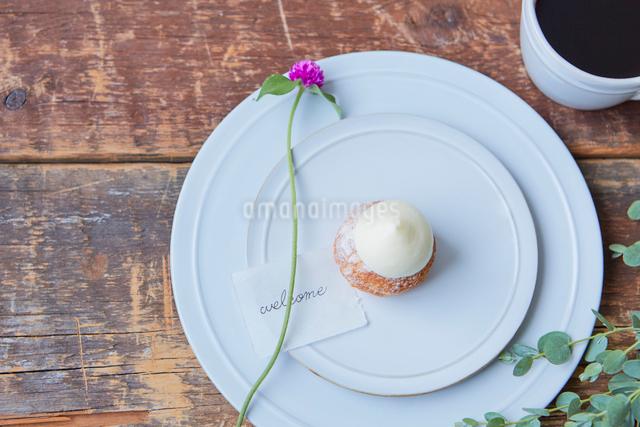 味のある天板の上のユーカリと皿に乗ったシュークリームの写真素材 [FYI03114853]