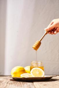 瓶詰めの蜂蜜とそのまわりに置かれたレモンの写真素材 [FYI03114869]