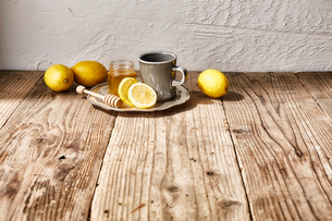 蜂蜜とグレーのマグカップと周りに置かれたレモンの写真素材 [FYI03114870]
