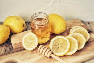 カッティングボードの上に置かれた蜂蜜と輪切りのレモンの写真素材 [FYI03114873]