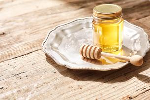 シルバーの皿の上に置かれた瓶詰めの蜂蜜の写真素材 [FYI03114874]