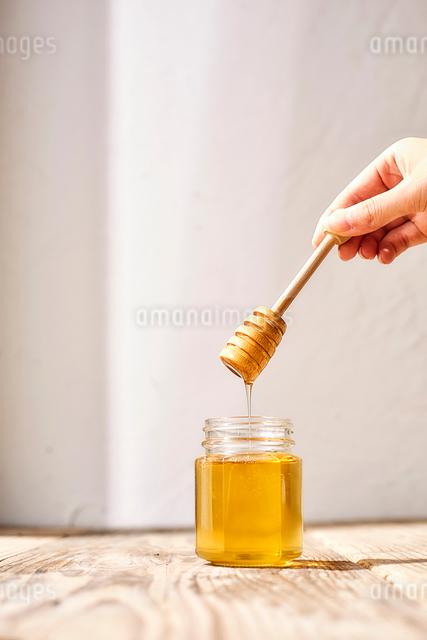 瓶詰めの蜂蜜とはちみつスプーンを持つ女性の手の写真素材 [FYI03114878]
