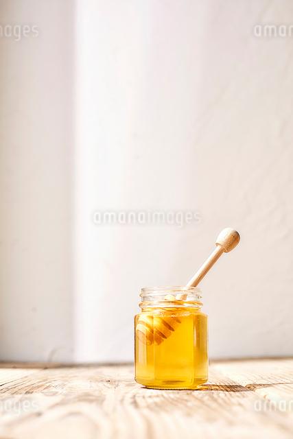 瓶詰めの蜂蜜と瓶にささったはちみつスプーンの写真素材 [FYI03114879]