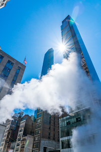ミッドタウン マンハッタンの高級高層コンドミニアムと漂うスティームを照す太陽。の写真素材 [FYI03115048]