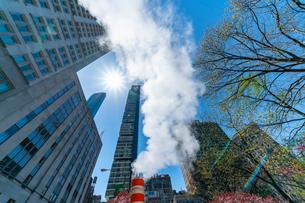 ミッドタウン マンハッタンの高級高層コンドミニアムと漂うスティームを照す太陽。の写真素材 [FYI03115066]