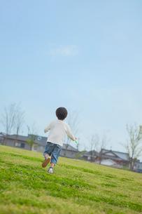 草原を走る男の子の写真素材 [FYI03118126]
