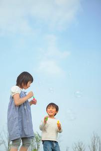 シャボン玉で遊ぶ姉弟の写真素材 [FYI03118135]