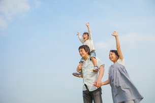 青空の下に立つ3人の日本人家族の写真素材 [FYI03118137]