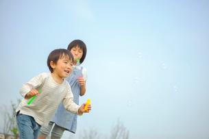 シャボン玉で遊ぶ姉弟の写真素材 [FYI03118140]
