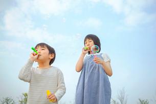 シャボン玉で遊ぶ姉弟の写真素材 [FYI03118151]