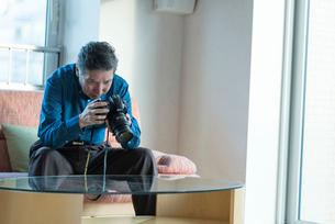 カメラをいじるシニアの男性の写真素材 [FYI03118596]