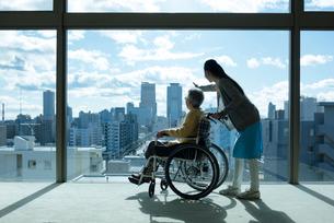 車椅子の老夫婦を介助するホームヘルパーの写真素材 [FYI03118603]