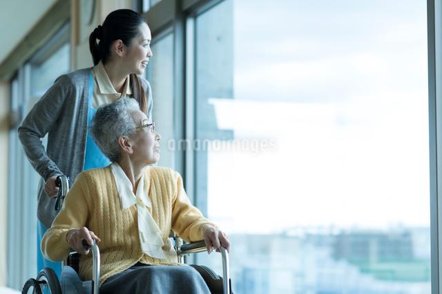 車椅子の老夫婦を介助するホームヘルパーの写真素材 [FYI03118606]