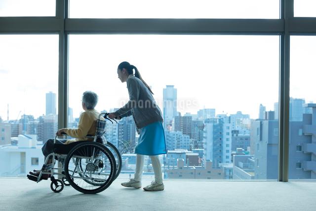 車椅子の老夫婦を介助するホームヘルパーの写真素材 [FYI03118607]