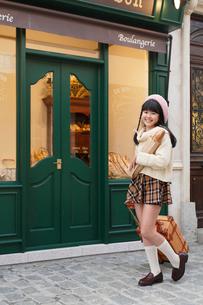 パン屋の前に立つ女の子の写真素材 [FYI03118784]