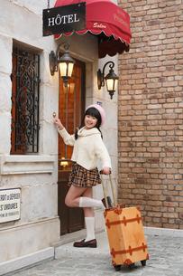 おしゃれなホテルの前に立つ女の子の写真素材 [FYI03118788]