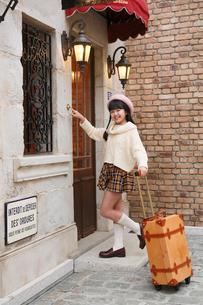 おしゃれなホテルの前に立つ女の子の写真素材 [FYI03118795]