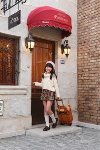 おしゃれなホテルの前に立つ女の子の写真素材 [FYI03118797]