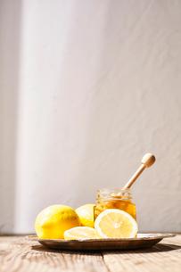 瓶詰めの蜂蜜とそのまわりに置かれたレモンの写真素材 [FYI03119594]