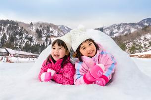 雪山でカマクラに入る子供の写真素材 [FYI03121194]