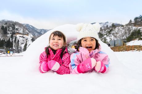 雪山でカマクラに入る子供の写真素材 [FYI03121195]