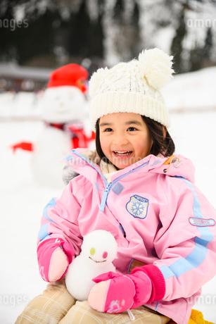 雪山で雪だるまを持つ子供の写真素材 [FYI03121199]