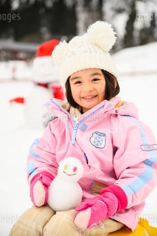 雪山で雪だるまを持つ子供の写真素材 [FYI03121200]