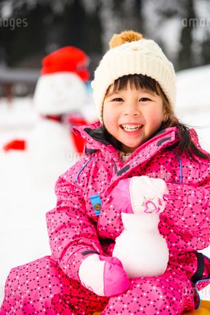 雪山で雪だるまを持つ子供の写真素材 [FYI03121202]