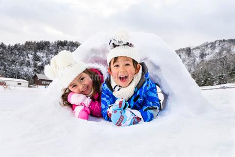 雪山でカマクラに入る子供の写真素材 [FYI03121260]