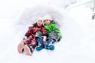 雪山でカマクラに入る子供の写真素材 [FYI03121410]