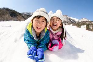 雪山でカマクラに入る子供の写真素材 [FYI03121447]