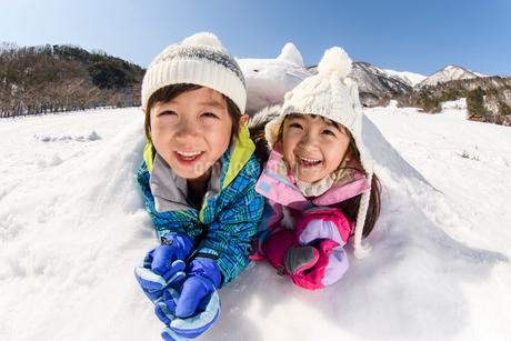 雪山でカマクラに入る子供の写真素材 [FYI03121448]