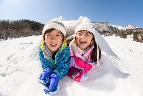 雪山でカマクラに入る子供の写真素材 [FYI03121450]