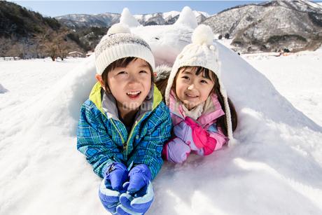 雪山でカマクラに入る子供の写真素材 [FYI03121452]