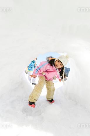 雪山でカマクラに入る子供の写真素材 [FYI03121457]