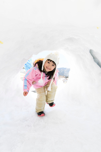 雪山でカマクラに入る子供の写真素材 [FYI03121458]