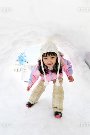 雪山でカマクラに入る子供の写真素材 [FYI03121459]