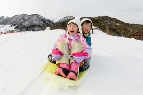 雪山でソリで遊ぶ子供の写真素材 [FYI03121478]