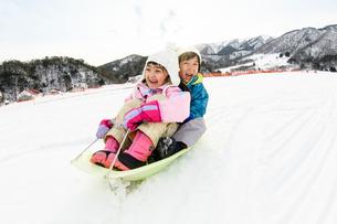 雪山でソリで遊ぶ子供の写真素材 [FYI03121479]