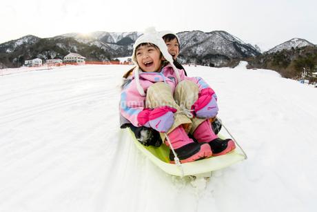 雪山でソリで遊ぶ子供の写真素材 [FYI03121480]